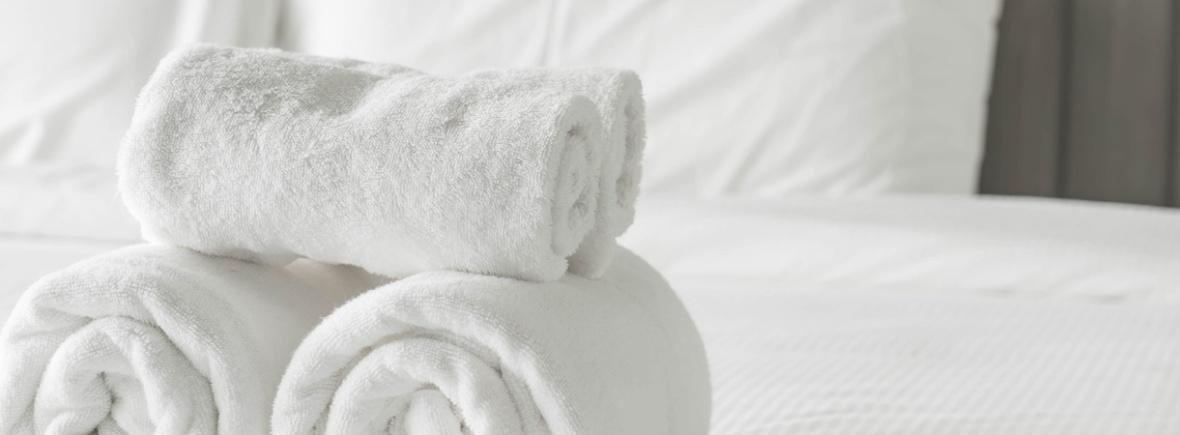 Бели кърпи, навити на руло, върху легло